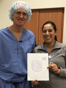 Dr. Gordon Baltuch and nurse practitioner Hanane Chaibainou pose with the final example of Neyhart's tremor suppression: a drawing of a spiral.