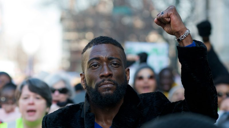 Prentice Bush raises his fist as he joins a crowd of hundreds protesting right-wing extremism at a march in Philadelphia, on Martin Luther King Jr. Day. (Bastiaan Slabbers for WHYY)