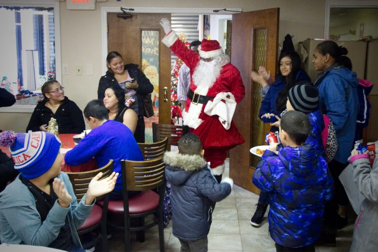 Santa makes an appearance at a  Christmas party for Puerto Rican families at the office of Association of Puerto Ricans In March, on Philadelphia Saturday, for about 20 families displaced from Puerto Rico after hurricane Maria. (Bastiaan Slabbers for WHYY)