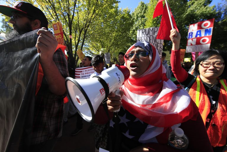 Bangladeshi descent American Hoshneara Begum, center, leads chant of slogans against what they call a