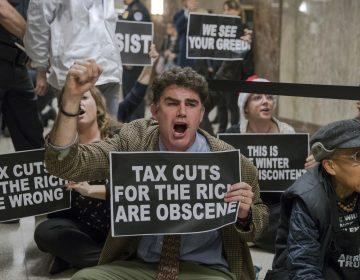 Protesters shout their disapproval of the Republican tax bill outside the Senate Budget Committee hearing room on Capitol Hill in Washington, Tuesday, Nov. 28, 2017.