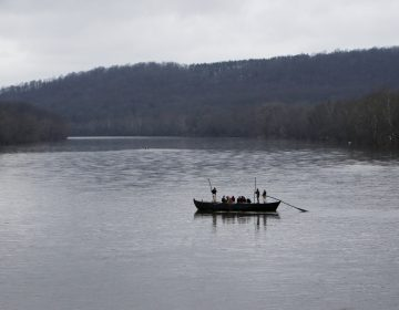 FILE- In this Dec. 25, 2015, file photo, a group of Revolutionary War re-enactors row a Durham boat during the re-enactment of Washington crossing the Delaware River, in Washington Crossing, Pa. Re-enactors might not be able to make their annual Christmas Day trip across the Delaware River between Pennsylvania and New Jersey because low water levels make it impossible for them to navigate their wooden Durham boats.