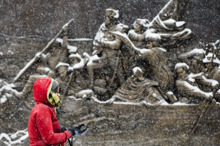 A person walks during a snowstorm past a sculpture of General George Washington crossing the Delaware River mounted on the Museum of the American Revolution in Philadelphia, Friday, Dec. 15, 2017. (AP Photo/Matt Rourke)