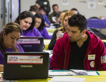 FILE - In this Monday, March 31, 2014 file photo, SEIU-UHW worker Kathy Santana, left, assists Ruben Torres, 27, during a health care enrollment event at the SEIU-UHW office in Commerce, Calif.