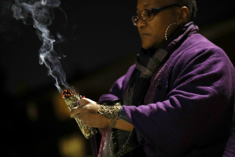 In this Dec. 11, 2017 photo, Erricka Bridgeford burns sage as she performs a ceremony near the scene of a homicide in Baltimore. Bridgeford lost a brother, a stepson, and three cousins to gun violence. (Patrick Semansky/AP Photo)