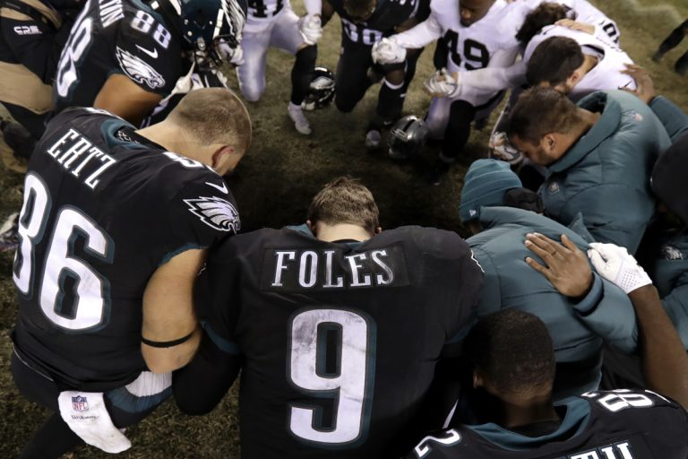 Philadelphia Eagles' Nick Foles (9) kneels with other players after an NFL football game against the Oakland Raiders, Monday, Dec. 25, 2017, in Philadelphia. Philadelphia won 19-10. (Michael Perez/AP Photo)