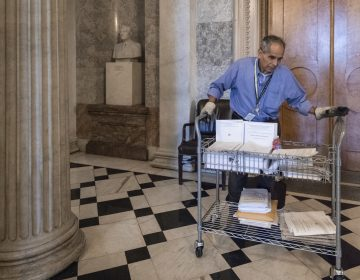 After senators worked past midnight to pass the Republican tax bill, Walter Arandia distributes copies of the daily legislative calendar before lawmakers return, on Capitol Hill, in Washington, early Wednesday, Dec. 20, 2017.