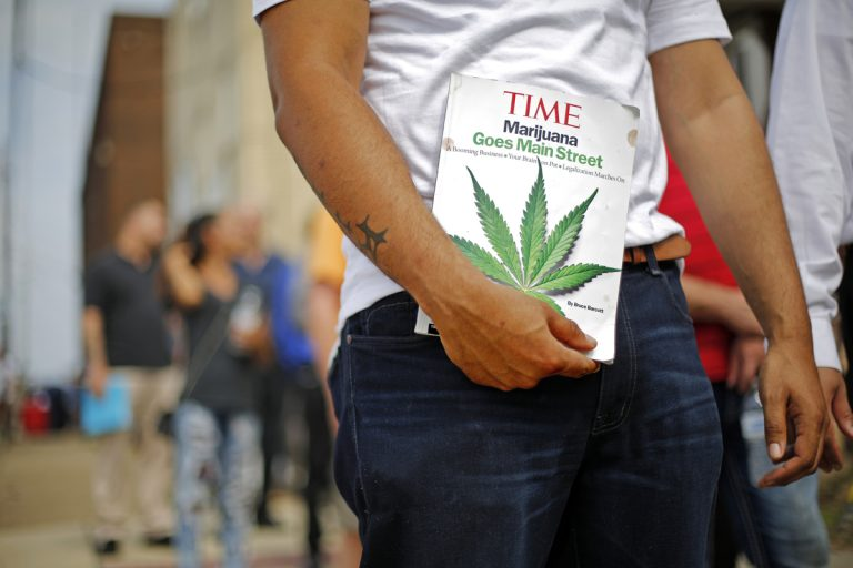 Michael Cole of Clairton, Pa., holds a Time magazine while waiting in line in downtown McKeesport, Pa., to attend a Medical Marijuana Job Fair, Thursday, July 27, 2017. (Gene J. Puskar/AP Photo)