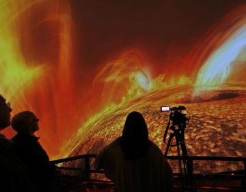 In this Wednesday, Dec. 6, 2017 photo, people watch interstellar bodies move through space during a media preview at the planetarium at Liberty Science Center in Jersey City, N.J. The  newly refurbished planetarium is the largest in the western hemisphere and uses ten advanced projectors to produce an 8K resolution. It opens to the public on Saturday, Dec. 9, 2017. (Seth Wenig/AP Photo)