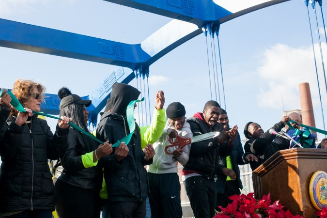 Members of the Youth Violence Reduction Parternship Guild who worked on the new mural on the B Street Bridge in Kensington cut the ribbon at the end of a dedication ceremony Tuesday. (Brad Larrison for WHYY)
