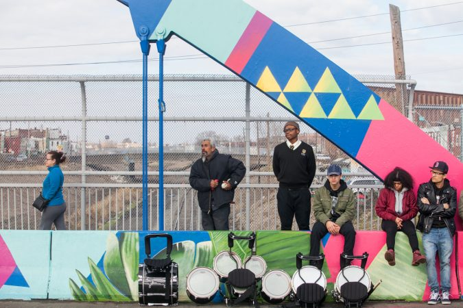 Community members and students from Kensington High School for the Creative and Performing Arts stood and walked on the B Street Bridge during a dedication ceremony for the recently-completed mural on the bridge. (Brad Larrison for WHYY)