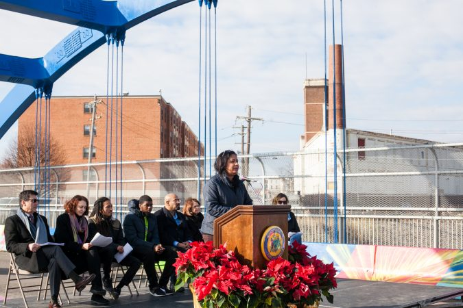 City Council Woman for the 7th District, Maria Quinones-Sanchez, spoke at the dedication ceremony for a new mural on the B Street Bridge in Kensington Tuesday. (Brad Larrison for WHYY)