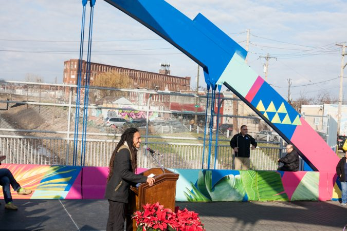 Lead artist Calo Rosa spoke at the dedication ceremony for the recently completed mural on the B Street Bridge in Kensington. (Brad Larrison for WHYY)
