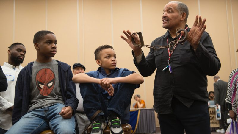 J. Justin Ragsdale holds up antique slave shackles during a demonstration on the conditions inside slave ships during the 2017 Black History and Culture Showcase in Philadelphia