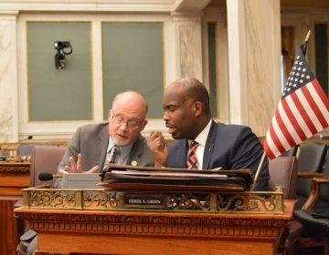 Councilmen Bill Greenlee (left) and Derek Green talk business during a hearing Monday.