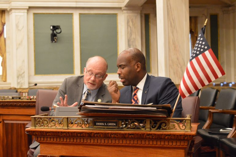 Councilmen Bill Greenlee (left) and Derek Green talk business during a hearing Monday.
