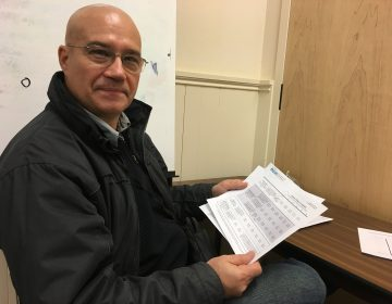 Gokhan Ozagacli looks over paperwork Thursday after enrolling for health insurance with the help of Pennsylvania Health Access Network. (Anne Hoffman/ for WHYY)