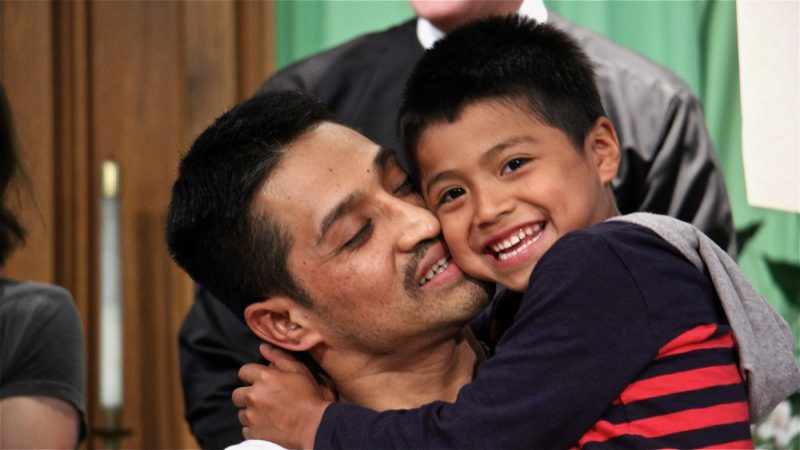 Javier Flores embraces his son, Javier, 5. Under threat of deportation, Flores, a father of three, found sanctuary at Arch Street United Methodist Church for more than 10 months. He left on Oct. 11, 2017, when authorities decided to defer action while his visa application is considered. (Emma Lee/WHYY)
