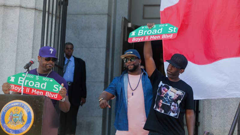 Boyz II Men with their newly unveiled Boyz II Men Boulevard signs stand in front of their alma mater the Philadelphia High School for Creative and Performing Arts. (Brad Larrison for NewsWorks) II Men