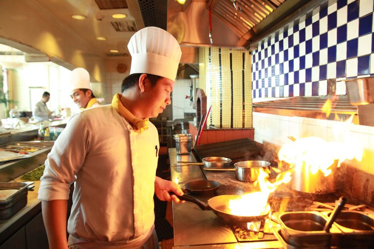 portrait of chef flambe cooking in the kitchen