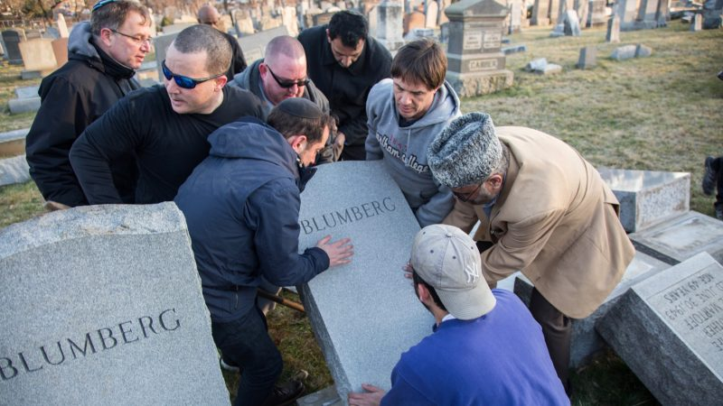 Members from the local Jewish community are joined by members of the Philadelphia chapter of the Ahmadiyya Muslim Center and others as they try to put upright headstones that were vandalized at Mount Carmel Jewish Cemetary in Northeast Philadelphia. The vandalism was seen as part of a growing trend of anti-semitism sweeping the United States. More than 500 headstones were toppled and broken overnight February 26, 2017. (Emily Cohen for NewsWorks)