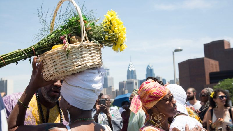 A woman carries offerings for the river goddess Oshun at the begining of the Philadelphia Odunde Festival. (Emily Cohen for WHYY)