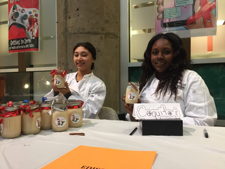 Keilina Collazo (left) and Elima Patterson, students at Edison High School, offer their homemade coquito for sale. (Avi Wolfman-Arent/WHYY).