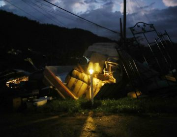 A donated solar lamp in a driveway illuminates storm debris still waiting to be collected earlier this week in Morovis, Puerto Rico. (Mario Tama/Getty Images)