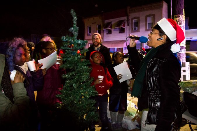Asteria Vives (right) and the girls club from the Lenfest Center sing holiday carols at 2nd and Indiana Streets in Kensington. (Kimberly Paynter/WHYY)
