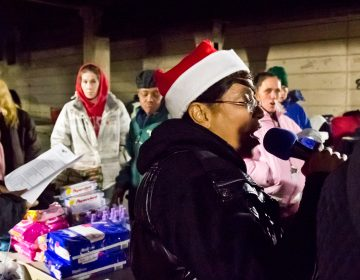 Asteria Vives, head of Home Quarters and Friends, sings carols at the Emerald Street and Lehigh underpass, in the Kensington section of Philadelphia. (Kimberly Paynter/WHYY)