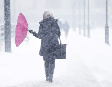 A pedestrian's umbrellas is upset during a winter snowstorm