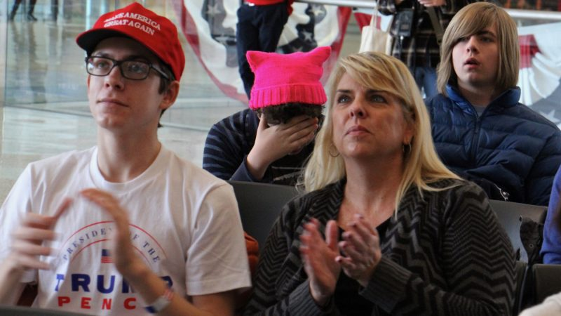Thomas Dintino, 16, (left) and his mother Karen, from Marlton, New Jersey, applaud as Donald Trump is sworn in as president while Dashiell Ward, 15, of Philadelphia, looks away. About 50 people watched the inauguration on the big screen at the National Constitution Center. (Emma Lee/WHYY)