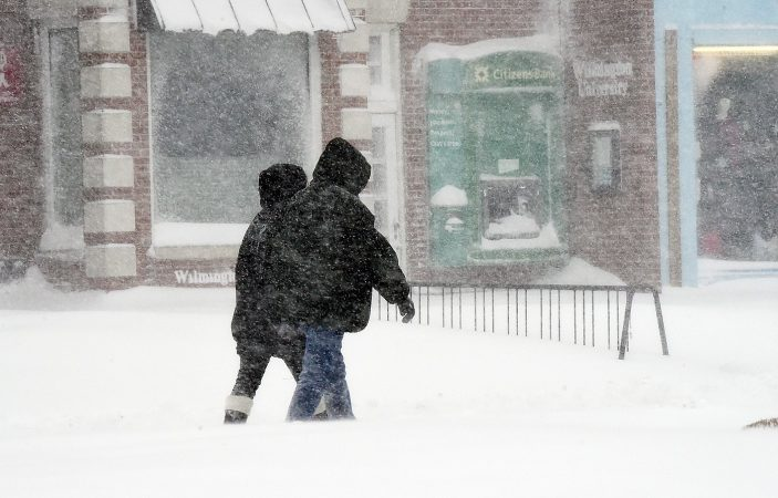 A few people ventured out to walk amid the blowing and drifting snow in Rehoboth Beach. (Chuck Snyder/for WHYY)