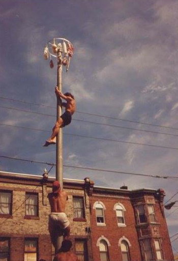 Frank Longo nears the top of the pole in the 1993 competition at the Italian Market Festival.
