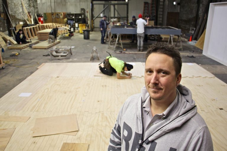 Matthew Lewandowski stands in the Philadelphia Scenic Works workshop where set builders from three different small theater groups find space to work at the same time.