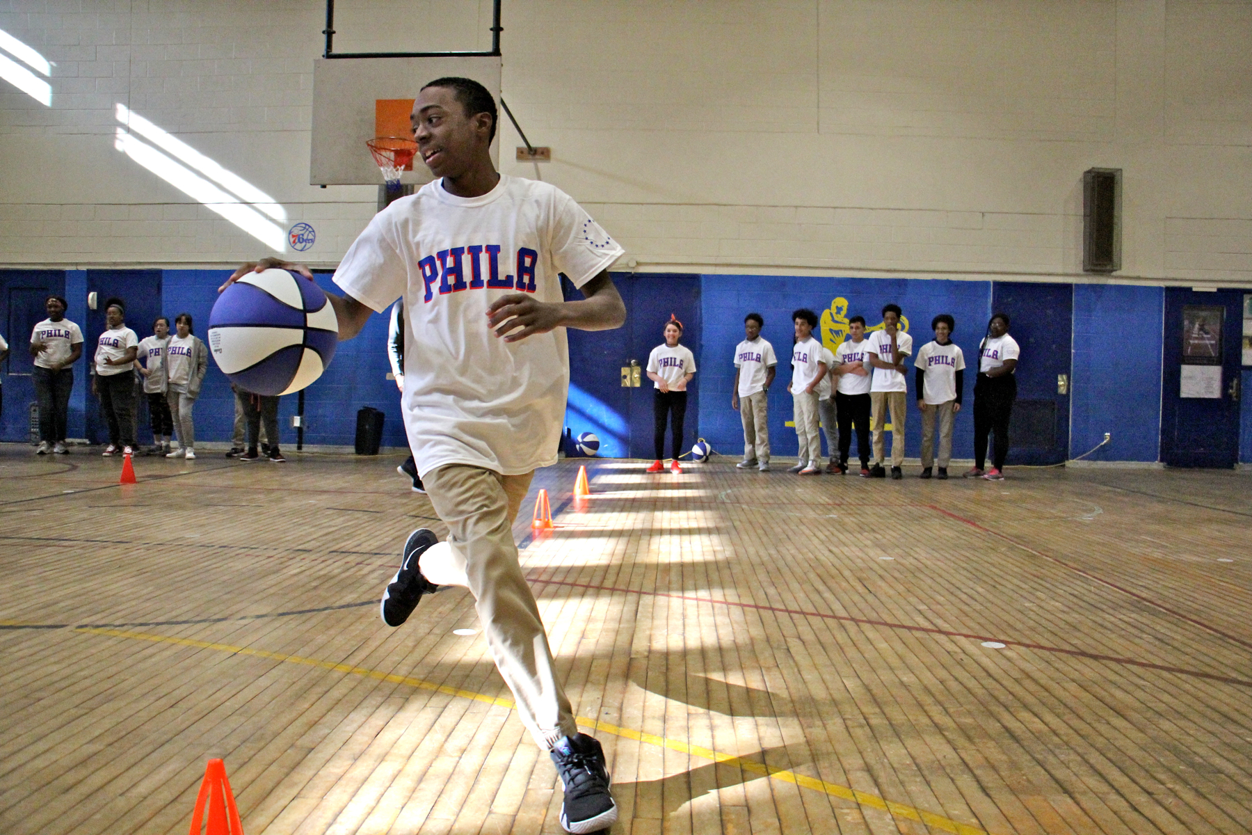 Eighth grader Phillip Bland and his classmates enjoy a Sixers basketball clinic at their school.