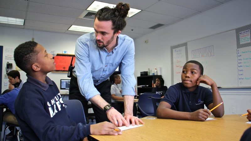 Jeremiah Johnson (left) works on his rap lyric with counselor Luke O'Brien while Ahmad Jackson (right) looks on. (Emma Lee/WHYY)