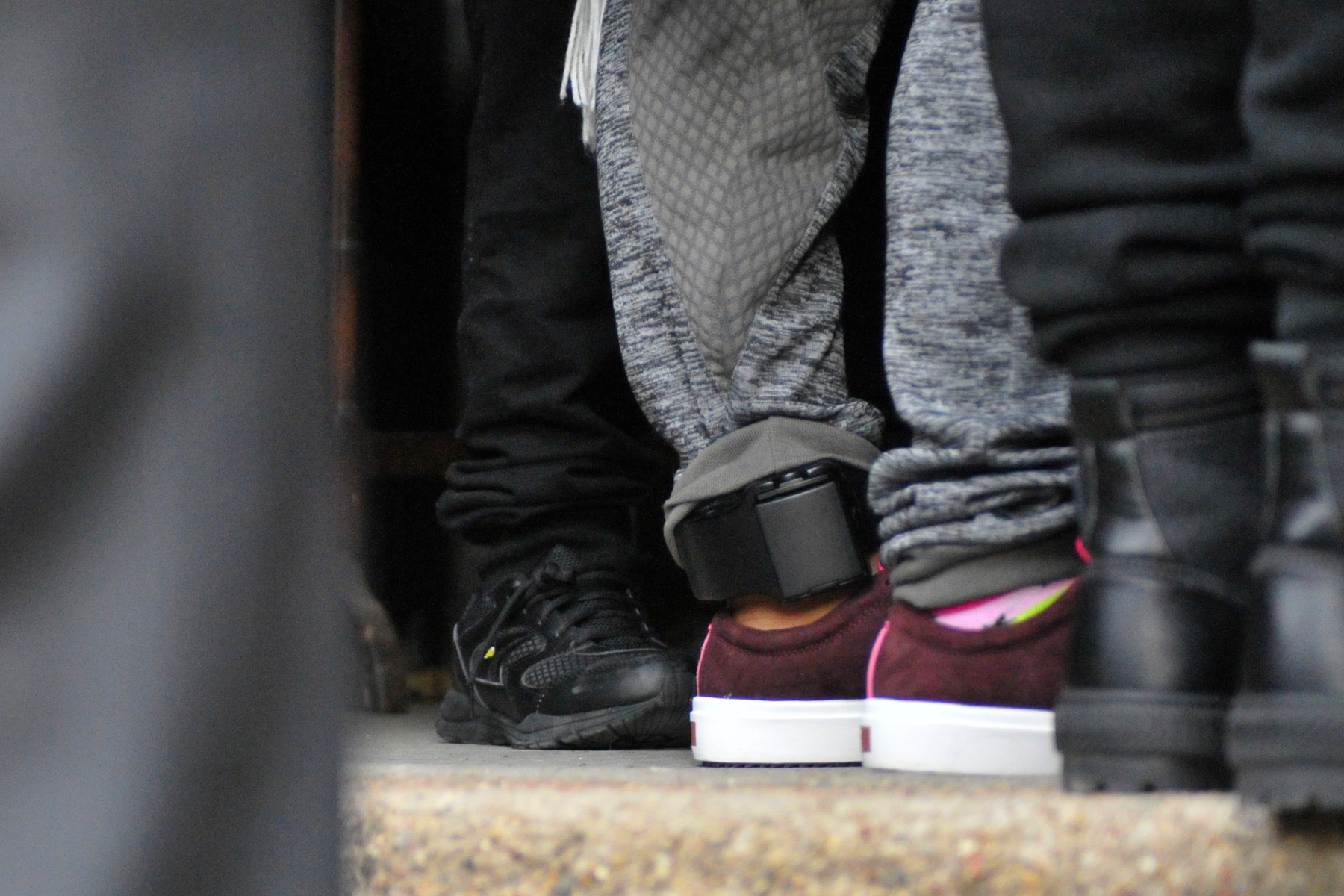 The ankle monitor worn by Camela Apolonio Hernandez is visible as she sees her children off in the doorway of her sanctuary at Church of the Advocate in North Philadelphia.