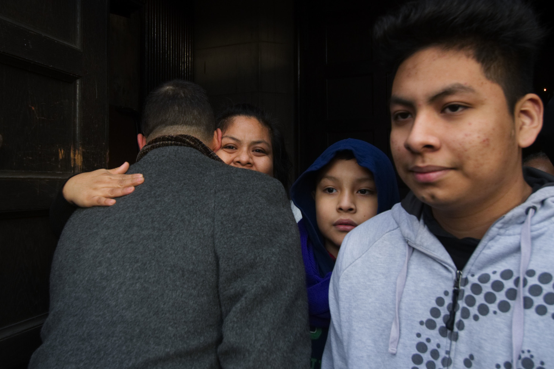 State Rep. Chris Rabb and Camela Apolonio Hernandez embrace in the doorway of Church of the Advocate in North Philadelphia as her four children leave sanctuary to go back to school for the first time since the family received a deportation order.