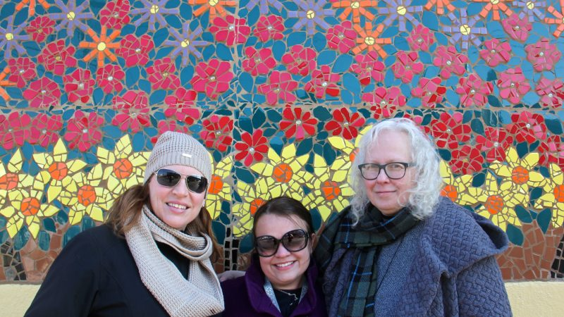 Standing in front of one of the McClure School murals (from left) Principal Shanon Marino, art teacher Becky Naughton, and teaching artist Kimberly Niemela look forward to completing the project this year.