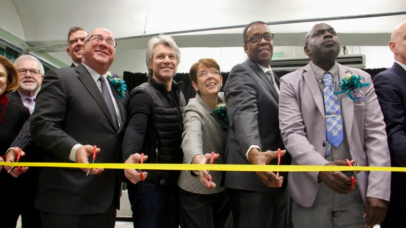 Sister Mary Scullion (center) of Project Home flanked by rocker philanthropist Jon Bon Jovi and City Councilman Darrell Clarke, helps cut the ribbon to open the Hub of Hope, a refuge for homeless people in the Center City subway concourse. (Emma Lee/WHYY)