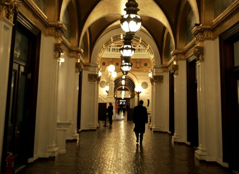 A man walks down a hall toward the light of the Capitol rotunda, in Harrisburg, Pa.