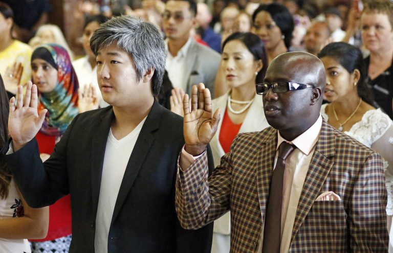 Immigrants from 23 countries recite the Oath of Allegiance during the naturalization ceremony