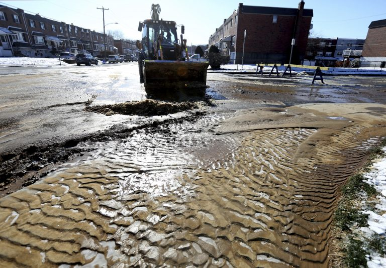 Mud and ice are cleared from the road during cleanup after a water main break last week in Northeast Philadelphia. City workers are dealing with about 20 water main breaks a day, officials say.