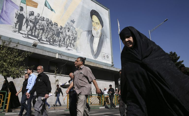 Iranian worshippers walk past a painting of the late revolutionary founder Ayatollah Khomeini and Basij paramilitary force members, at the conclusion of a Friday prayer ceremony in Tehran, Iran, Friday, Oct. 13, 2017. (Vahid Salemi/AP Photo)