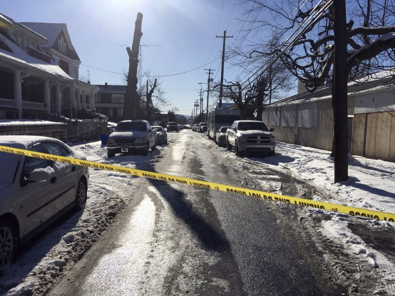 Crime tape stretches across a road near the scene of a shooting Thursday, Jan. 18, 2018, in Harrisburg, Pa. The mayor of Harrisburg said a U.S. marshal is dead after being shot while serving an arrest warrant in the city. Mayor Eric Papenfuse said two other officers were wounded in the Thursday morning shooting. (Marc Levy/AP Photo)
