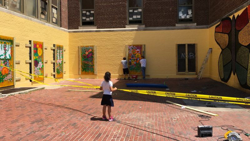 A student watches as paintings are installed in the McClure School courtyard.