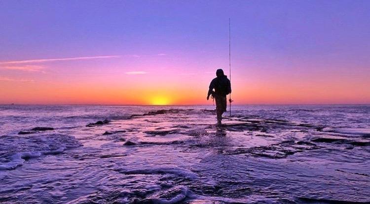 An angler walks a jetty in Asbury Park. (Photo: Suzanne Spitaletta)