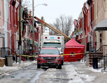 The investigation continues at the scene of a row house fire on North Colorado Street that killed a firefighter and a 61-year-old resident.