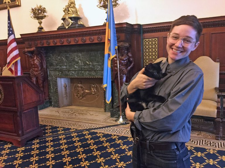 Guthrie Conygham, manger of ACCT's off-site adoption unit, holds Missy, an adoptable kitten, at City Hall. (Kyrie Greenberg for WHYY)